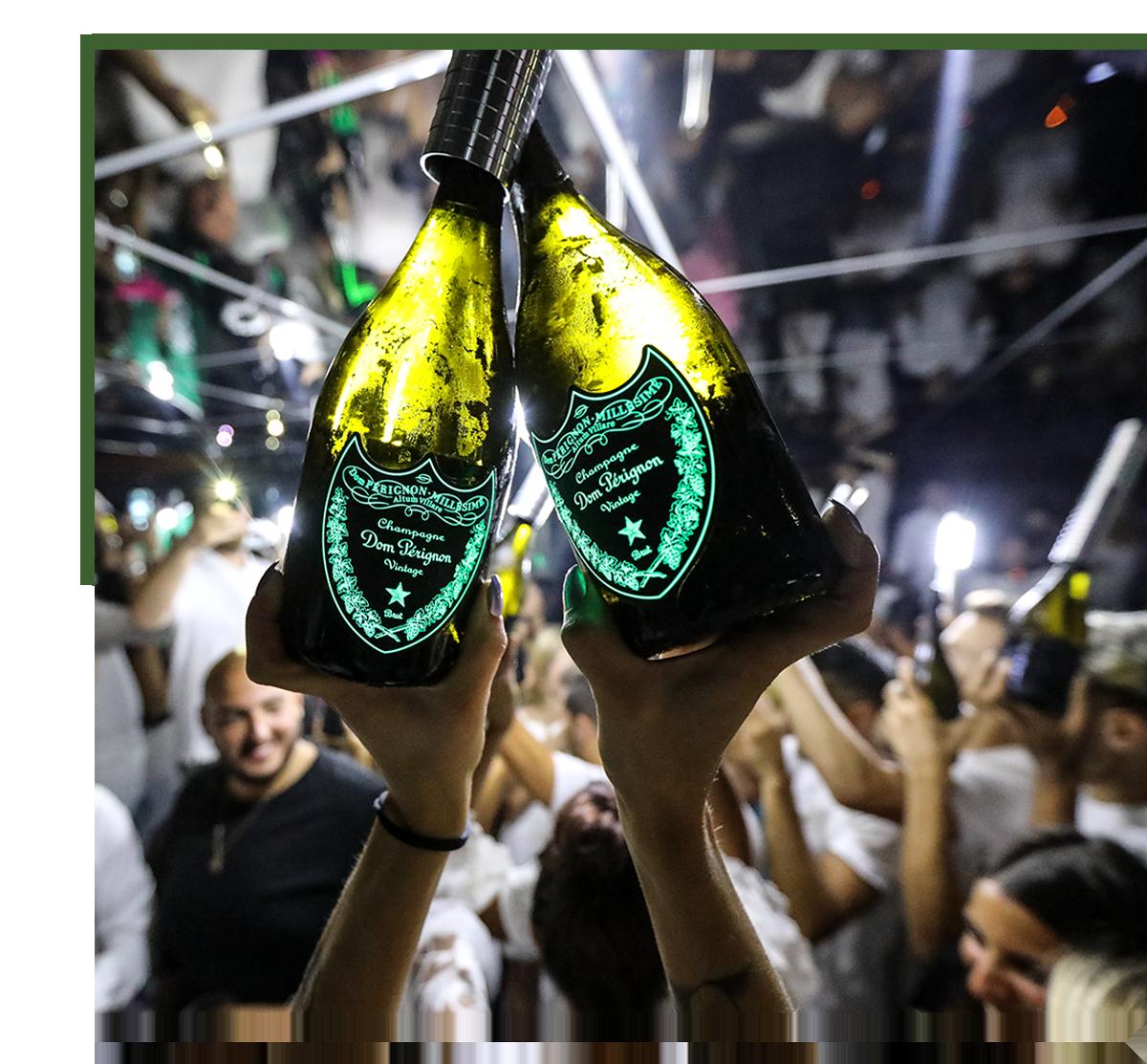 deux bouteilles de champagne dom pérignon tenues par des mains de femme dans le club bâoli cannes