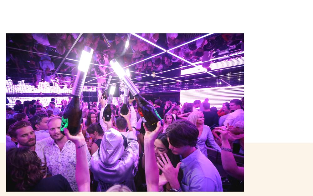 jeunes personnes qui dansent et distribuent des bouteilles de champagne au club bâoli