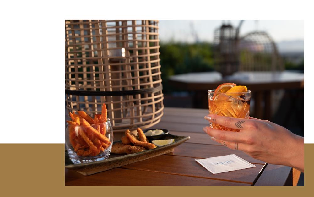 dégustation d'un cocktail sur la terrasse du cloud nine avec une planche de nourriture et un bandeau doré en fond