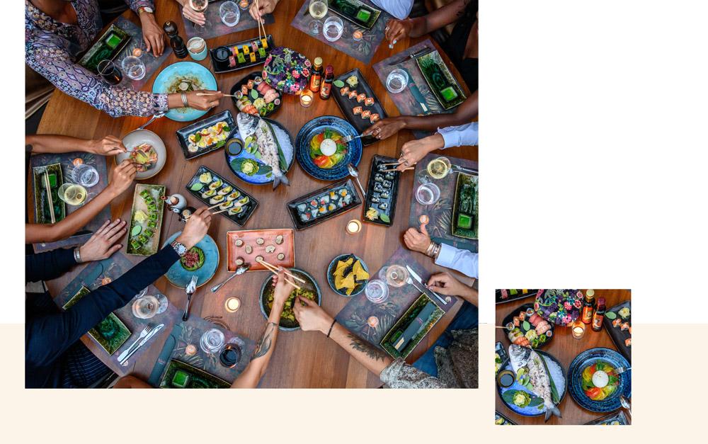 grande table au restaurant bâoli à cannes avec des plats de poisson et sushi à partager entre amis